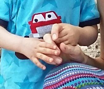 man sieht in Grossaufnahme ein kleines Kind, welches sich mit seinen zwei Händen an der Hand der Mutter anhält, die neben ihm hockt