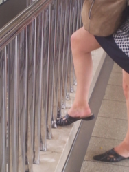bei einem Aluminiumgeländer stützt eine Frau mit Minirock das eine Bein auf den Sockel, um in ihrer Tasche was zu suchen, sexy