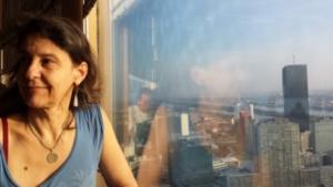 ich sitze am Fenster des Donauturms und schaue lächelnd in den Raum, vor dem Fenster die Skyline von WIen, mit Spiegelung