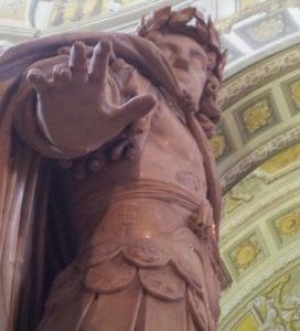 die Steinfigur eines Römers, der eine abweisende Hand nach unten hält in Richtung Betrachter