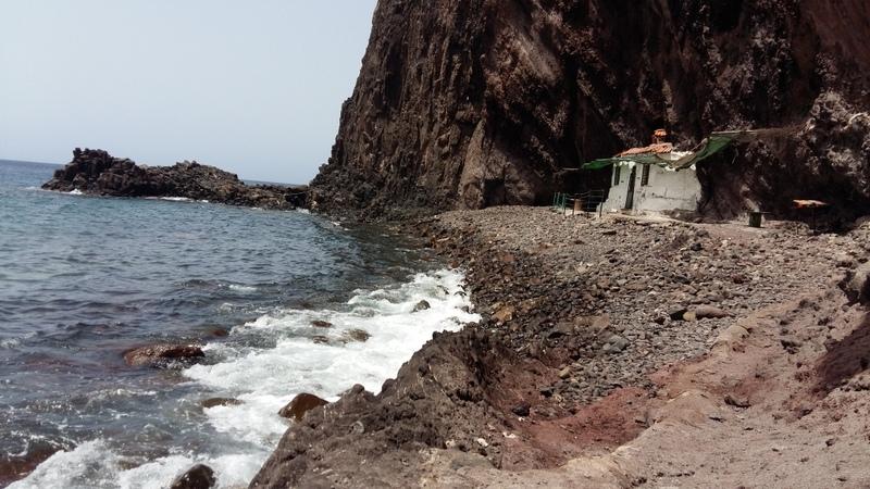 ein altes, kleines, weisses Haus am Strand, welches in die hoch aufragende Klippe hineingebaut ist