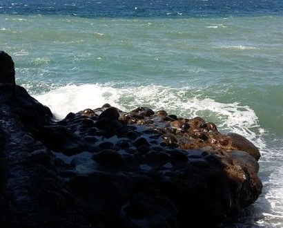 aus dem Schatten von Lavagestein heraus, umspielen Meereswellen den Stein