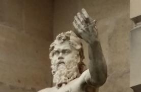 männliche Statue aus Stein hebt linken Arm in Erhabenheit