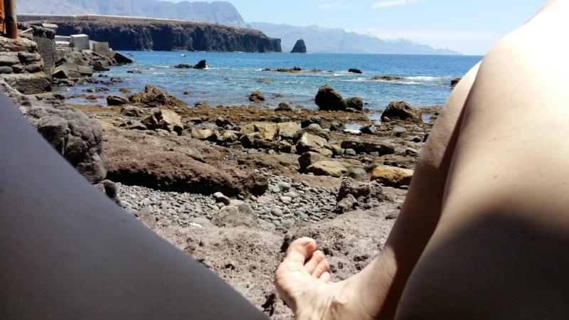 Steinstrand, in 10 metern beginnt das Meer, der Blick geht in eine Bucht, im Hintergrund sieht man in Farbschattierungen die Felswände aus dem Wasser aufragen, ich liege am Strand und man sieht meine Oberschenkel, durch die ich hindurchfotografiert habe, sexy