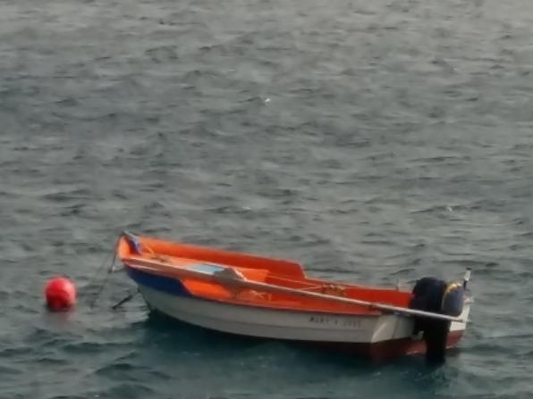 ein kleines Boot mit roter Boje schwimmt auf dem Meer, ausser Wasser sieht man im HIntergrund nur einen schmalen Weg in der Mitte zwischen zwei Felswänden durch