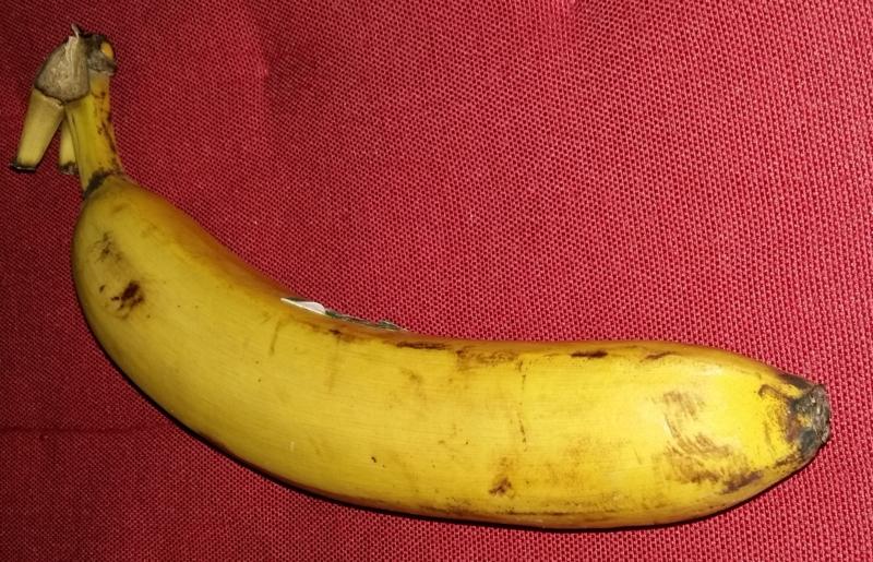 das Bild zeigt eine Banane auf rotem Grund