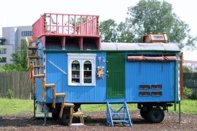ein blauer Bauwagen mit grüner Tür vor der eine blaue Treppe steht, ein weisses Fenster und ein rosa Balkon am Dach zeugen davon, dass das ein umgebauter Fantasiewohnwagen sein soll