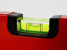 man sieht die Linse einer roten Wasserwaage in Grossaufnahme