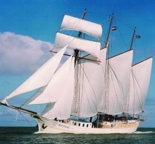 ein Dreimaster-Segelschiff mit geblähten Segeln auf offener See