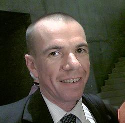 Porträt von Bart Weetjens, hageres längliches Gesicht, abrasierte stoppelglatzige Haare, dunkle Augen, mit einem Lächeln auf den Lippen,circa 50 Jahre alt