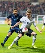 zwei Fussballer kämpfen im Dribbling um den Ball, im Hintergrund sieht man die anderen Spieler, das Tor und die Zuschauer im Stadion