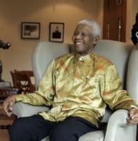 der alte Nelson Mandela, lachend in den Raum schauend, in einem Ohrensessel sitzend