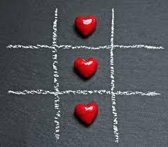 mit Kreise gezeichnetes Raster mit neun Feldern und in den drei mittleren liegen jeweils ein rotes Dekorherz, symbolisch: die Liebe gewinnt immer