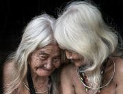 zwei weisshaarige alte, total verrunzelte Frauen mit langen Haaren, im Porträt, sitzen offenbar nackt, die eine, mit abgewandtem verschmitztemLächeln, die andere ist der ersten zugewandt. Die weissen Haare schulterlang beide, schön frisiert wie von jungen Frauen
