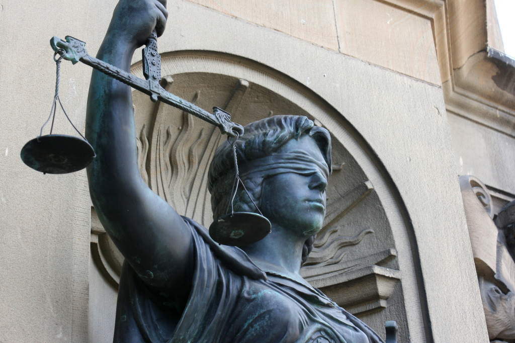 der Oberteil der Statue der Justitia, der Göttin der Gerechtigkeit, mit Großaufnahme auf die verbundenen Augen und die hochgehaltenen Waagschalen in ihrer Hand