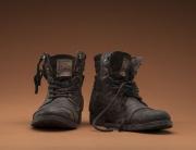 vor einem neutralen Hintergrund stehen zwei abgetragene Schuhe mit hohem Schaft und Schnürriemen