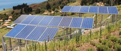 18 Sonnenkollektor-Panneele in drei Reihen angeordnet stehen auf Stelzen an einem Abhang