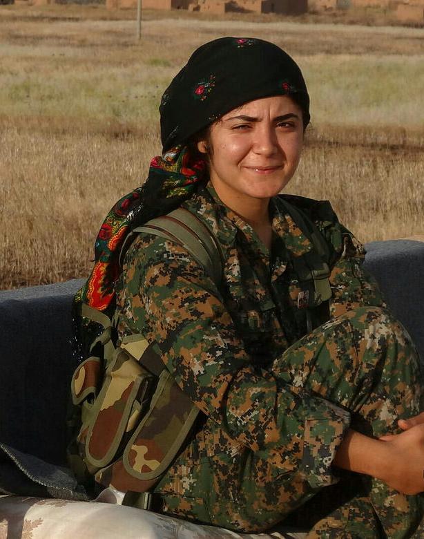 eine muslimische selbstbewusst in die Kamera verhalten lächelnde junge Frau in Tarnanzug