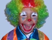 ein circa 8-jähriger Bub als extrem bunter Colwn verkleidet inklusive Perücke mit den Regenbogenfarben, er lacht lauthals in die Kamera