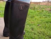 man sieht sitzende Beine, in den Knien abgewinkelt, und die Füße stecken in Gummistiefeln der Marke Aigle, seitlich an den Absätzen pickt nasses Gras, also ist die Person, man vermutet männlich, gerade übers Gras gegangen, man sieht die Wiese im Hintergrud