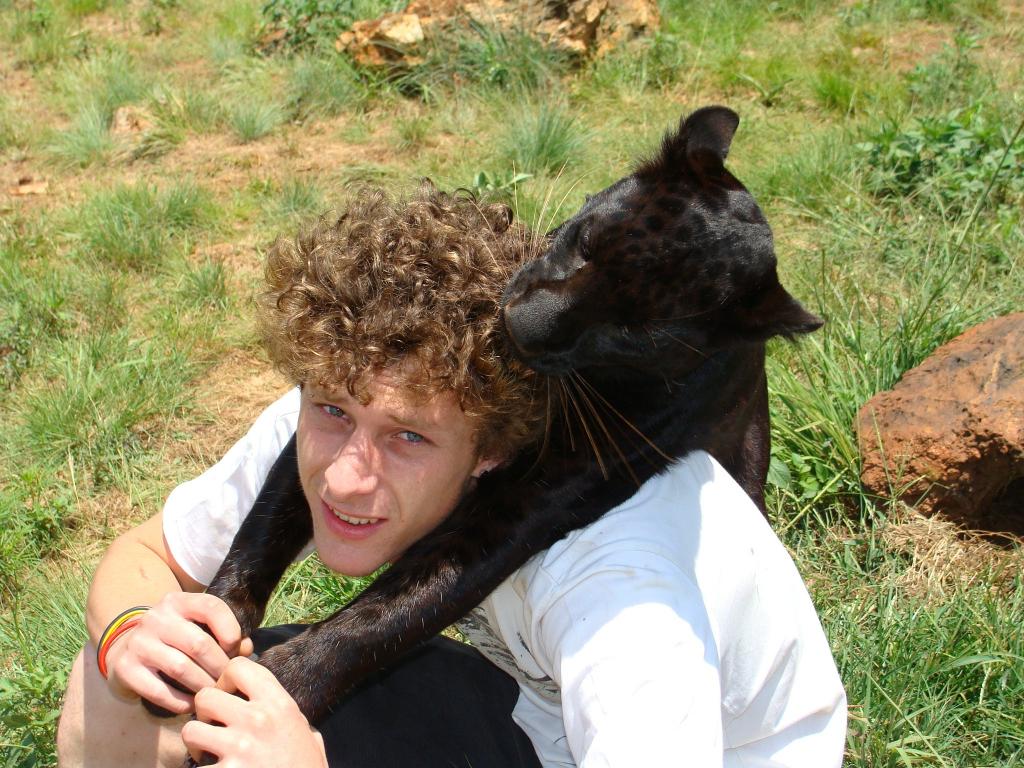 ein jugendlicher Mann mit blondem Lockenkopf sitzt in Wiese mit Blick in die Kamera und von hinten hat ihn ein schwarzer Leopard umarmt