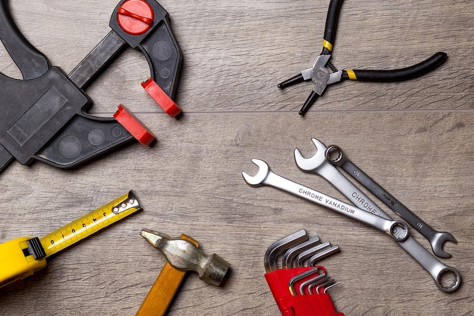 Werkzeug auf einer Holzplatte nebeneinander aufgelegt, ein Set Imbus-Schlüssel, drei Schraubenschlüssel, ein Hammer, eine Zange, ein Metermaß und eine Zwinge