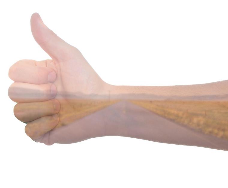 ein Unterarm und eine Hand, autostoppend den Daumen gehoben, Steppenlandschaft drübergeblendet.