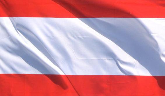 die rot weiss rote Fahne von Österreich vor blauem Himmel, sich bewegend im Wind