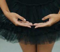 eine Ballerina mit beiden Händen vor dem schwarzen Ballettrock in groß