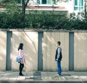 ein Mann und eine Frau stehen sich im Abstand vor einem Holzzaun gegenüber