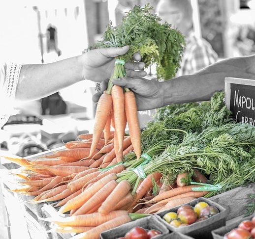 eine Hand greift nach einem Bündel Karotten, welches ihr eine andere Hand reicht