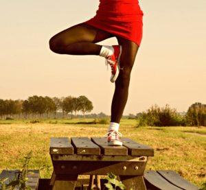 auf einem Holztisch in einer Heidelandschaft steht eine Frau auf einem Bein