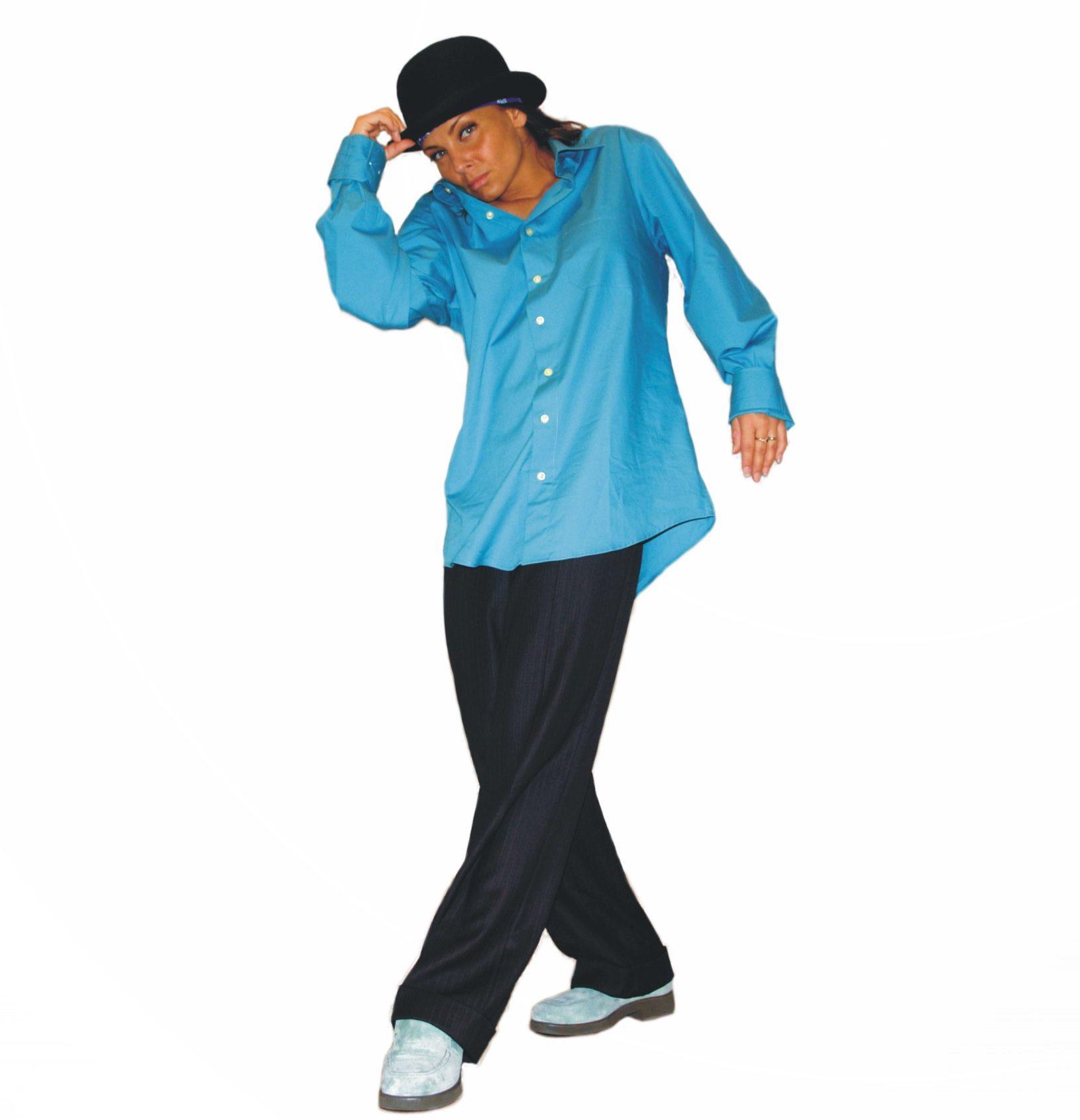 eine Frau in losem Gewand, mit blitztürkisem Hemd auf männlich gekleidet mit einem Zylinder am Kopf