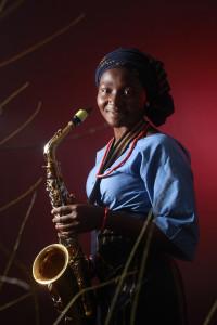 schwarze Frau mit Saxofon schaut lächelnd in die Kamera, Hintergrund in rot