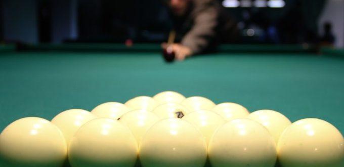 im Vordergrund sind die Billardkugel in Position Spielstart, im Hintergrund sieht man unscharf einen Spieler, der den ersten Stoss mit seinem Kö anvisiert