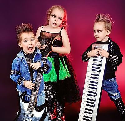 drei punkig gekleidete und frisierte Kinder spielen auf Rockgitarristen mit E-Gitarre und Keyboard