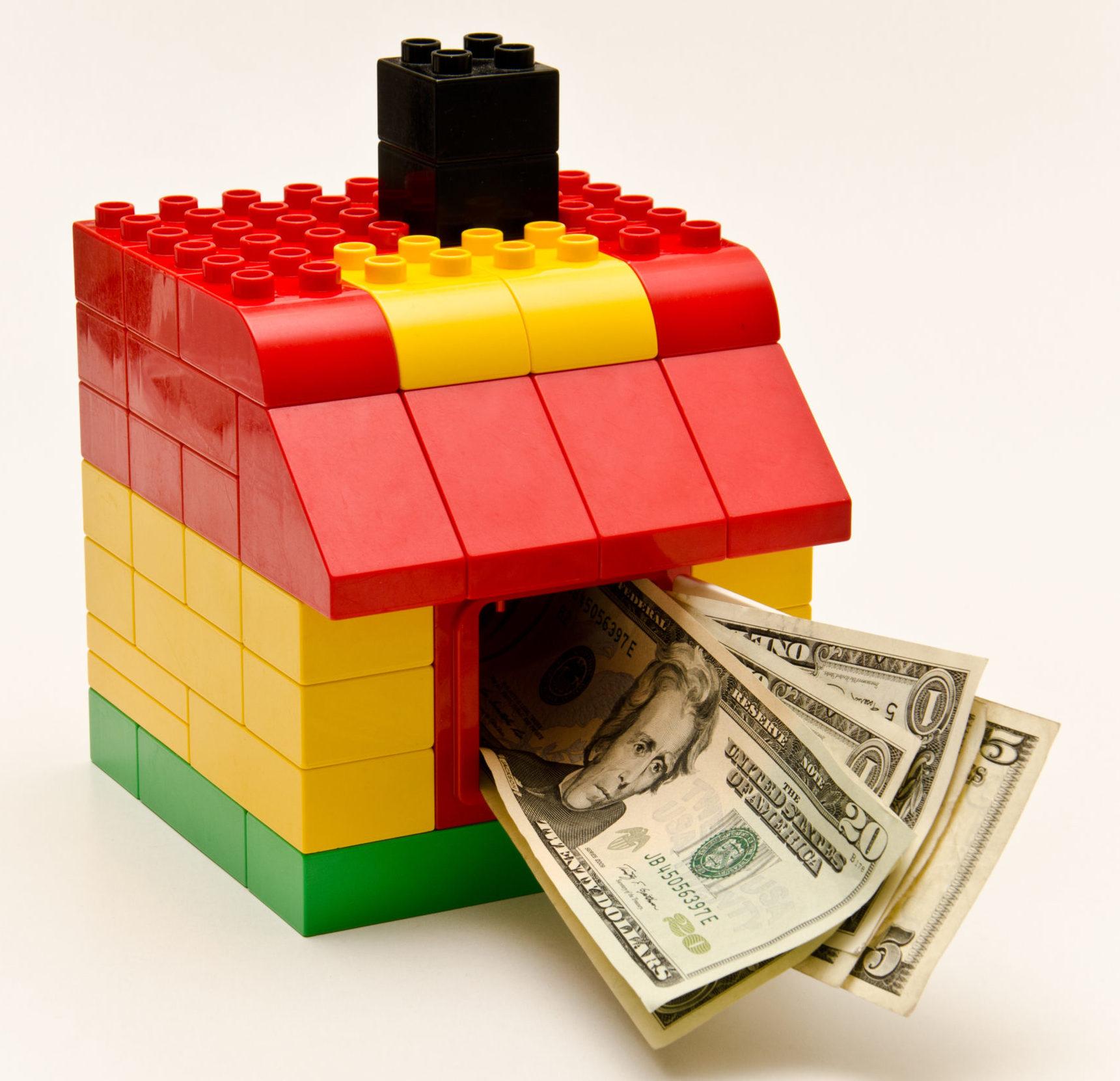 ein kleines buntes Legohaus, wo Dollarscheine drinsteckend rausschauen aus dem Fenster