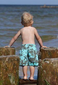 ein Kleinkind schaut in Badehose Richtung Meer, auf einer Holzkaimauer stehend