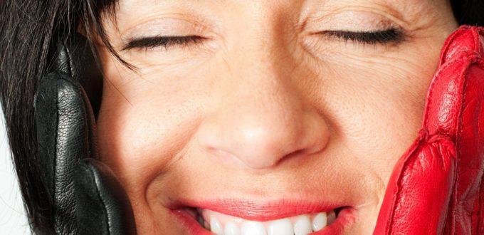 ein Porträt einer mit geschlossenen Augen glücklich strahlenden Frau mit dunklen kurzen Haaren,