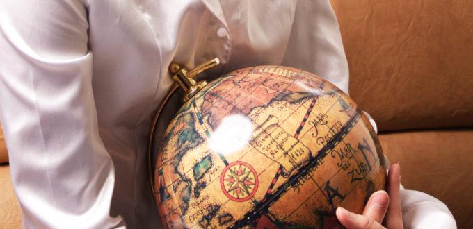 junge Frau hält versonnen lächelnd einen alten Globus umarmt auf dem Schoss