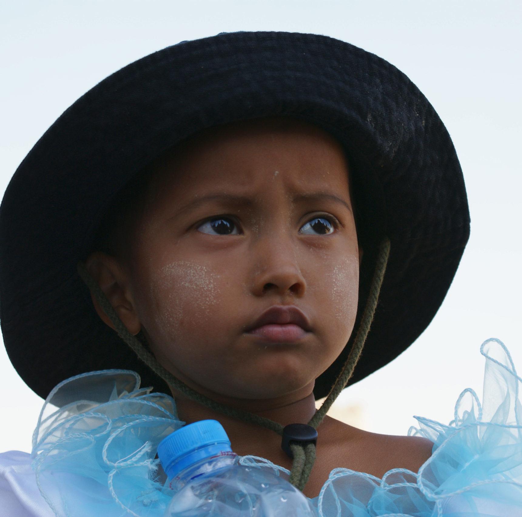 ein Mädchen aus Myanmar mit Hut mit Krempe schaut kritisch und ernst ins Weite, Porträt