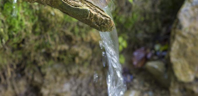 Quellwasser rinnt über ein halboffenes Holzrohr und fällt auf den natürlichen Boden, in Grossaufnahme