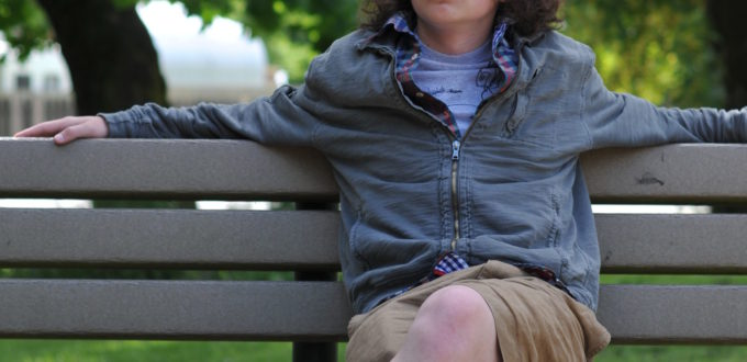 ein cooler Jugendlicher mit unfrisiertem Haar sitzt auf einer Bank in der Natur und schaut skeptisch, nachdenklich