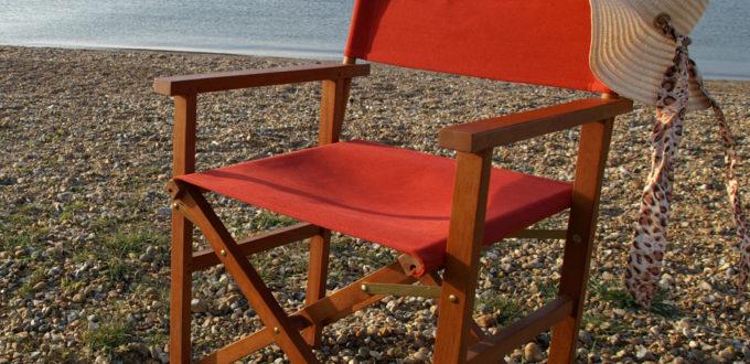ein roter Regie-Sessel steht am Strand, mit Meer im Hintergrund und einem weissen Frauenstrohhut über der Lehne
