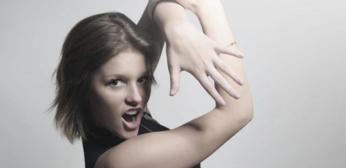 eine junge Frau macht eine ästhetische Abwehrgeste mit herausforderndem Blick in die Kamera