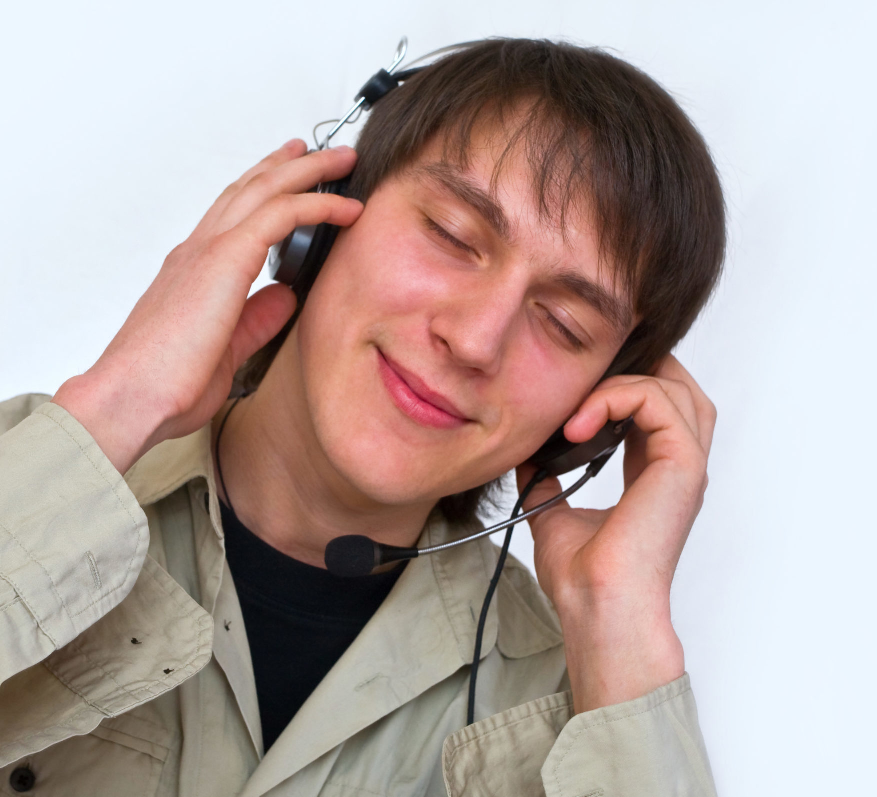 ein junger Mann hört über seine Kopfhörer Musik, mit geschlossenen Augen und einem seligen Lächeln auf den Lippen