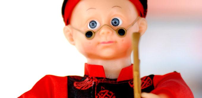 eine gutmütig blickende männliche Puppe mit kleiner Nickelbrille auf der Nase, in den Händen hält sie zwei Stäbe, die sie wie ein chinesisches Instrument geigenhaft aneinander zu reiben scheint