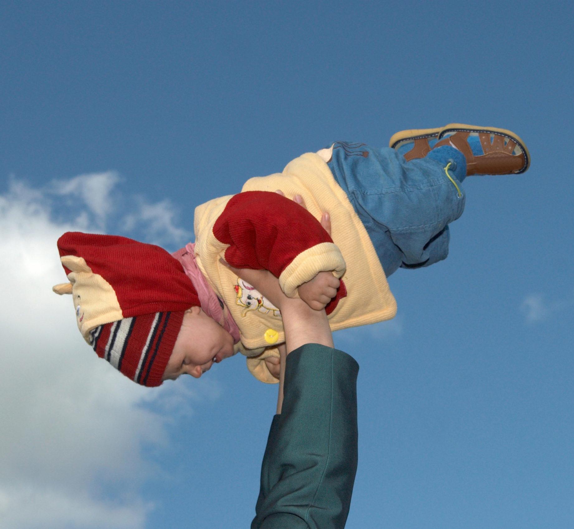 ein halbjähriges Kind, angepackt für winterliche Temperaturen, wird von zwei Armen im Spiel nach oben gehalten, im kindlichen Flugmodus