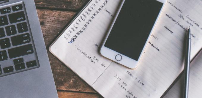 aufgeklappter Laptop, Handy und Notizheft in gross auf einem Schreibtisch liegend