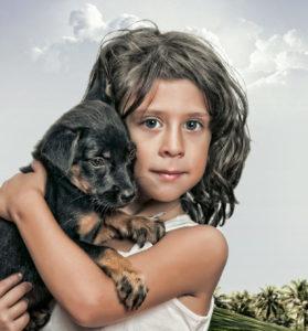 kleines Kind hält einen jungen schwarzen Hund im Arm und schaut verträumt in die Kamera